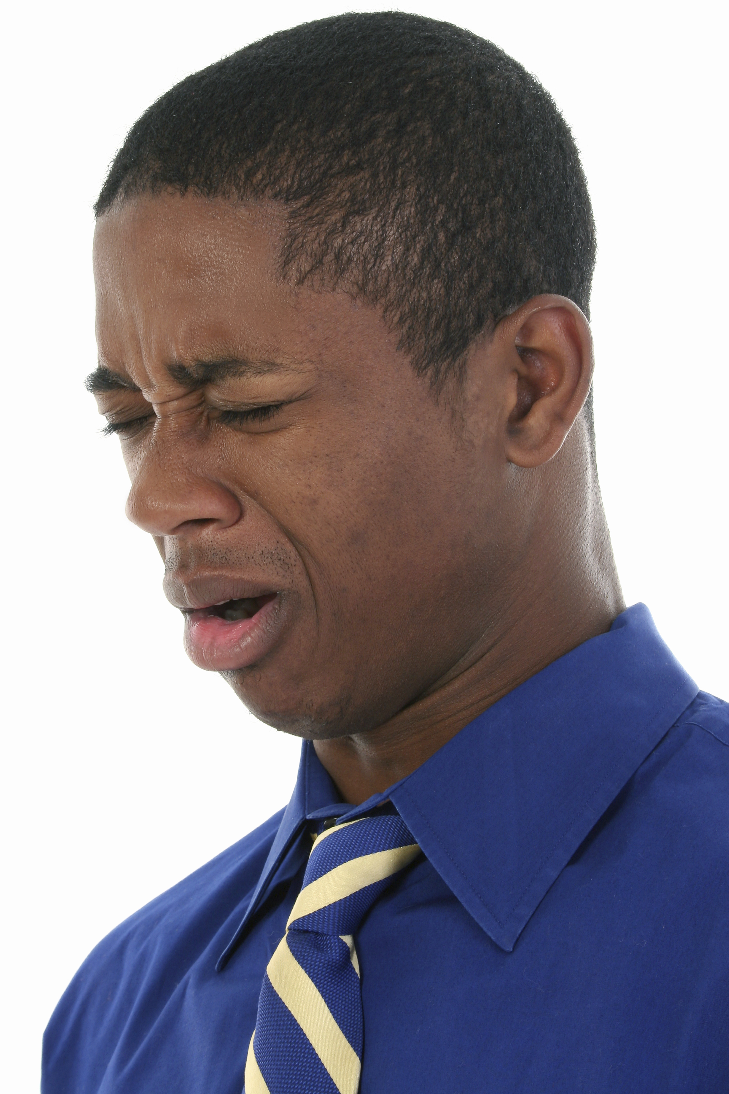 Close up headshot of African American man cringing from bad smell.  Wearing blue shirt and blue and yellow tie.